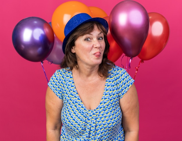 Funny and cheerful middle age woman in party hat holding colorful balloons  sticking out tongue celebrating birthday party standing over pink wall