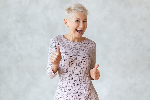 エレガントなペンシルドレスを着て踊り、承認のサインとして親指を立てるジェスチャーを示し、成功または有益な取引を祝い、広く笑顔で面白い陽気な中年のブロンドの女性