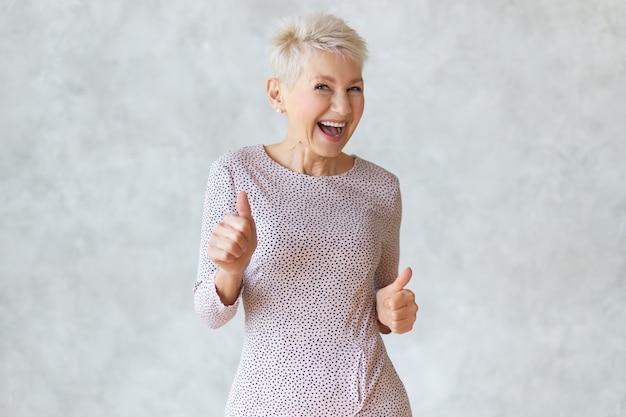 Divertente donna bionda di mezza età che indossa un elegante abito a matita ballando e mostrando il pollice in alto gesto come segno di approvazione, celebrando il successo o un affare redditizio, sorridendo ampiamente