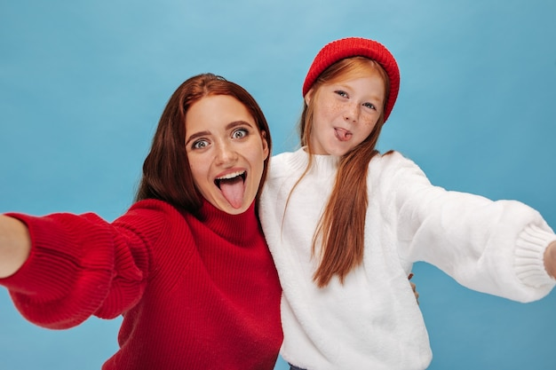 Funny cheerful two women in wide sweater showing tongues and takes selfie on isolated wall