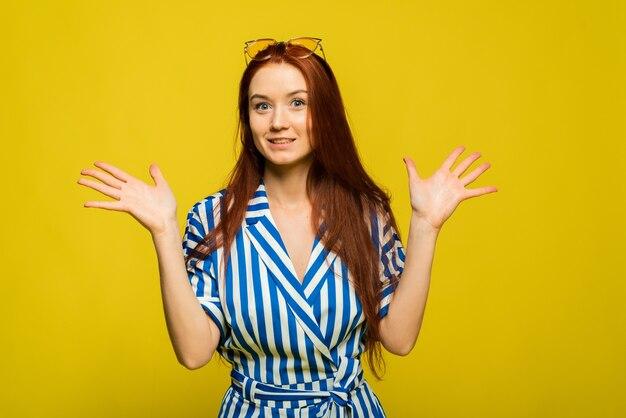 Смешная жизнерадостная женщина в желтых очках и синем комбинезоне на желтом фоне