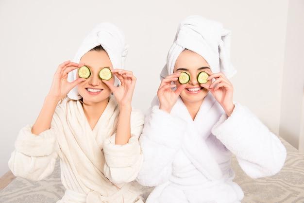 目にきゅうりと頭にタオルを持った面白い陽気な若い女性