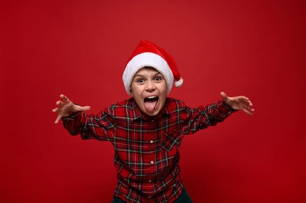 Забавный чирфул милый европейский малолетний мальчик в клетчатой рубашке и шляпе санта-клауса, морщась, глядя в камеру, позирует на красном фоне с копией пространства для новогодней и рождественской рекламы