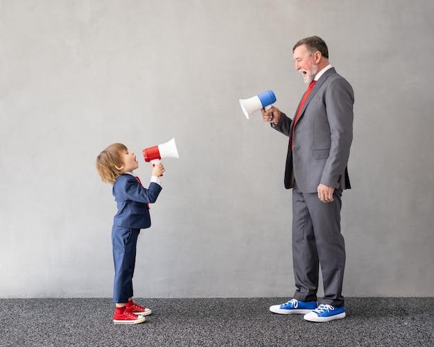 面白い子供と年配の男性はビジネスマンのふりをします。家で遊んでいる祖父と子供。教育、スタートアップ、ビジネスアイデアのコンセプト