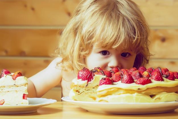 赤いイチゴとおいしいクリーミーなパイを食べる面白い子の赤ちゃん