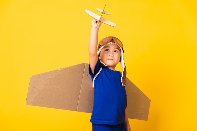 Funny child boy smile wear pilot hat play and goggles with toy cardboard airplane wings fly hold plane toy