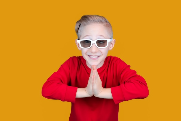 Funny child in children's 3d glasses puts his hands together and laughs