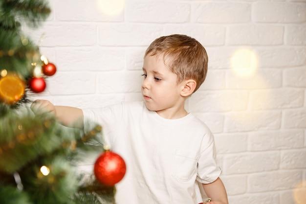 Забавный ребенок, украшающий елку шариками в канун рождества