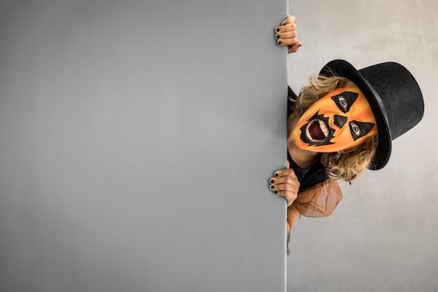 Смешной ребенок одетый костюм ведьмы держит баннер пустой хэллоуин осенний праздник концепция