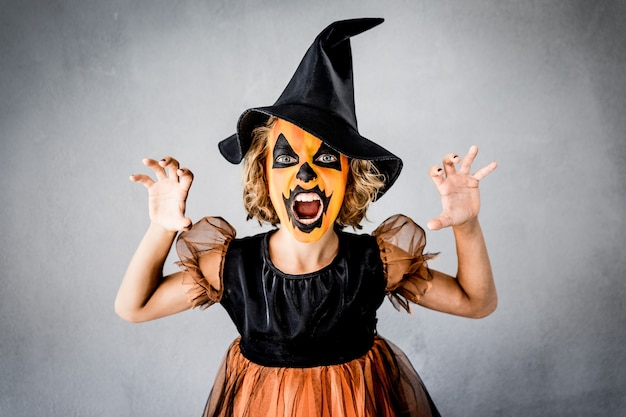 Смешной ребенок одетый костюм ведьмы. малыш нарисовал ужасную тыкву. концепция осеннего праздника хэллоуин