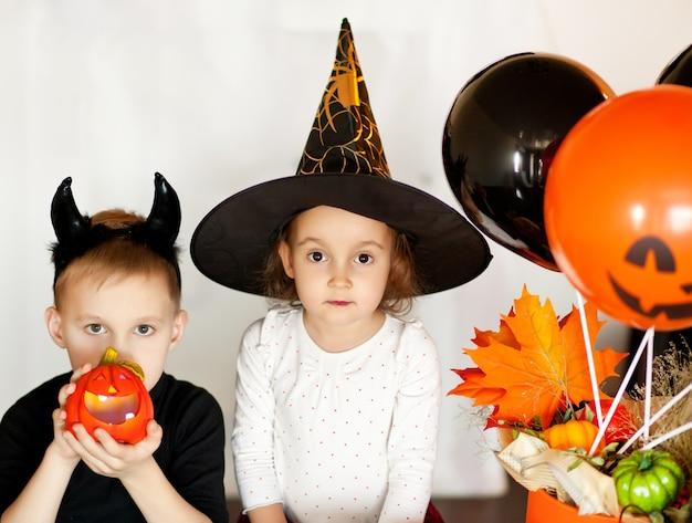 Забавная девочка и мальчик-подросток в костюмах ведьмы и зла для вечеринки на хэллоуин
