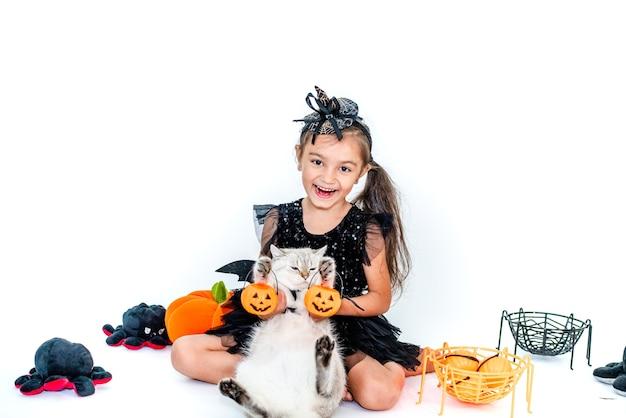 Смешная детская девочка в костюме ведьмы на хэллоуин с котом в костюме в руках