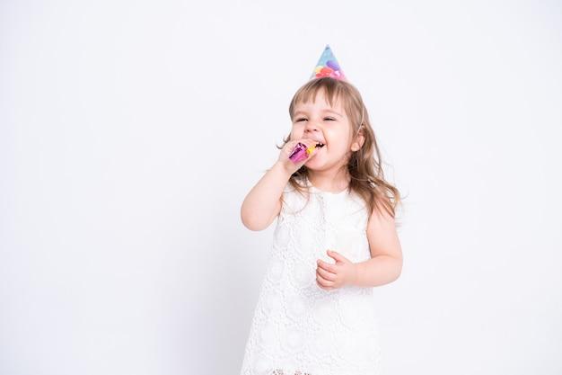 Смешная девочка ребенка в белом платье и шляпе дня рождения дует в свистке на белой поверхности.