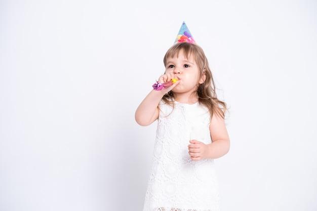 흰 드레스와 흰 벽에 휘파람을 불고 생일 모자에 재미 아이 소녀