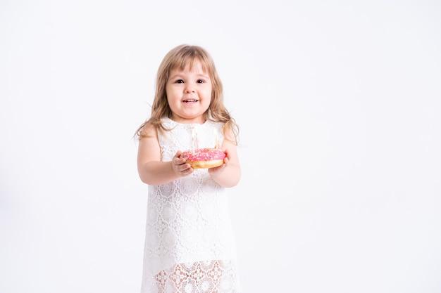 흰 벽에 촛불 생일 케이크 도넛과 흰 드레스에 재미있는 아이 소녀