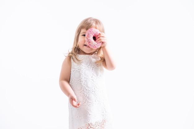 흰 벽에 핑크 도넛과 흰 드레스에 재미있는 아이 소녀