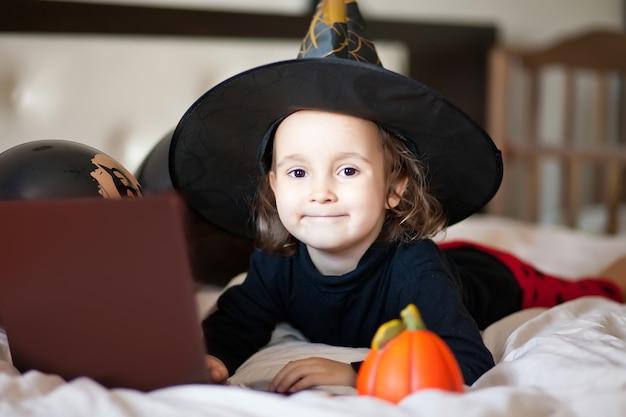 Забавная девочка в костюме ведьмы для хэллоуина лежит на кровати и использует портативный компьютер с цифровым планшетом. онлайн-звонок друзьям или родителям.