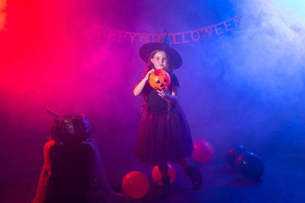 Смешная девочка ребенка в костюме ведьмы на хэллоуин с тыквой джек.