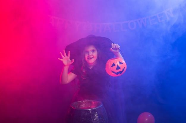 カボチャジャックとハロウィーンの魔女の衣装で面白い子の女の子。