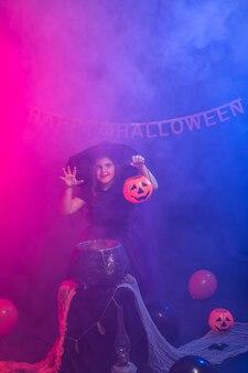 Смешная девочка ребенка в костюме ведьмы на хэллоуин с тыквой джеком.