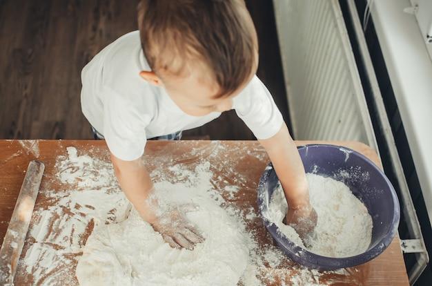 Забавная девочка готовит печенье, образ жизни, настоящий скандинавский интерьер, деревенский стиль, коричневый и красный деревянный фон