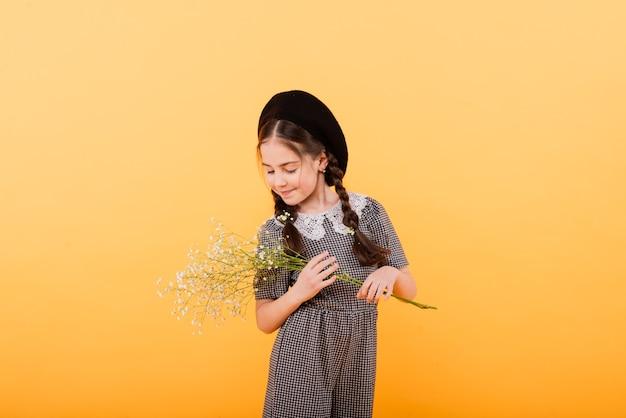 컬러 배경에 꽃의 부케와 함께 웃 고 재미있는 아이 소녀