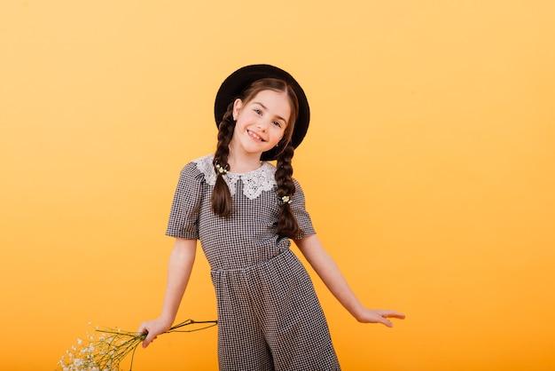 꽃의 부케와 함께 웃 고 재미있는 아이 소녀
