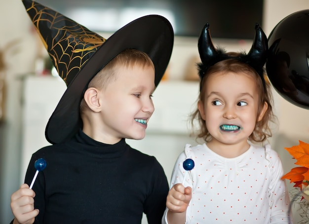 Funny child girl and teen boy in witch and evil costumes for halloween party eating candies lolly pops and have fun