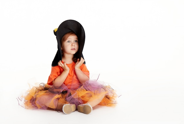 Funny child girl in witch costume for halloween on white