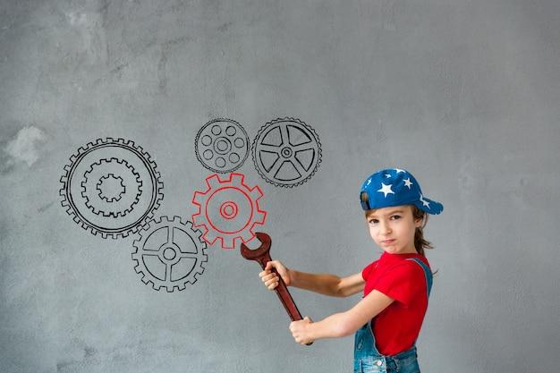 Забавный ребенок, держащий большой красный гаечный ключ. малыш играет дома. ремонт и дизайн-концепция