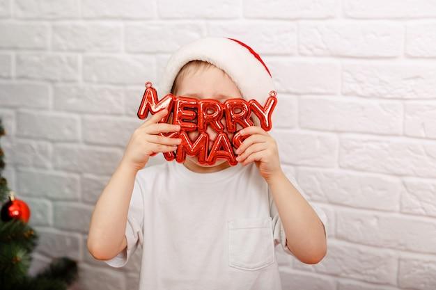 Забавный ребенок, держащий доску с надписью с рождеством, новым годом