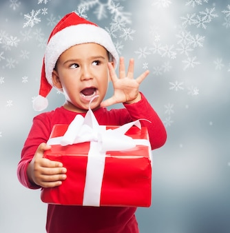 Funny child holding a christmas gift with his right hand