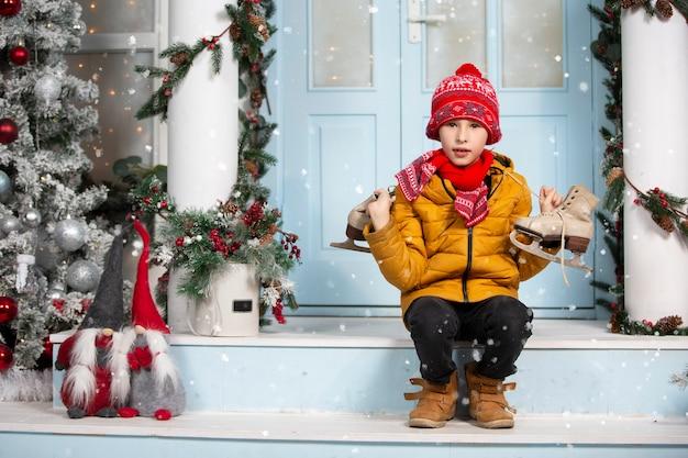 面白い子は古いスケート靴を持って、クリスマスツリーで飾られた家のポーチに座っています