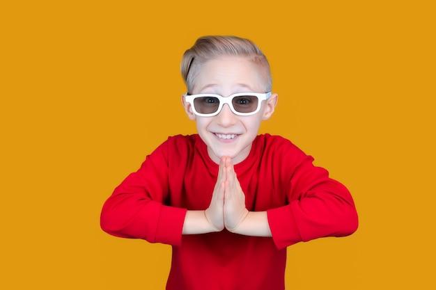 어린이용 3d 안경을 쓴 재미있는 아이가 손을 모으고 웃는다