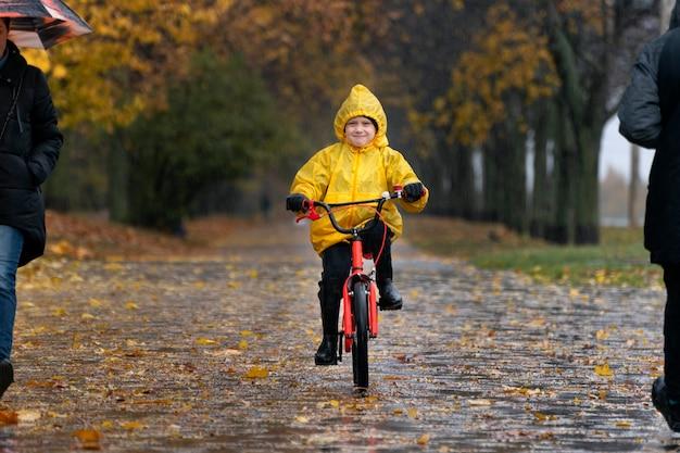 Забавный ребенок в желтом плаще едет на велосипеде в осеннем парке. мальчик едет по аллее в дождливом парке.
