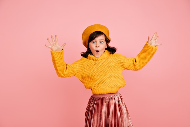 Funny child jumping with hands up.  carefree preteen girl in yellow sweater.