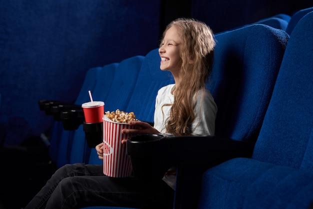 Забавный ребенок держит попкорн и смеется над комическим фильмом