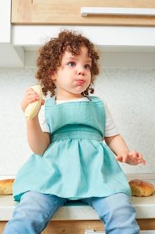 Забавный ребенок маленькая девочка сидит на столе с бананом в руке кушет кудрявый ребенок на кухне