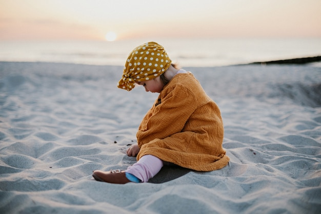 Funny child in oriental dress sitting on beach sand and playing with sand