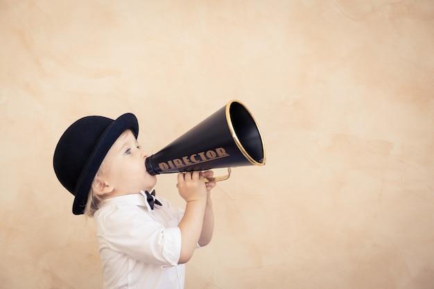 집에서 놀고 재미있는 아이. 빈티지 확성기를 통해 외치는 아이. 통신 및 복고풍 영화 개념