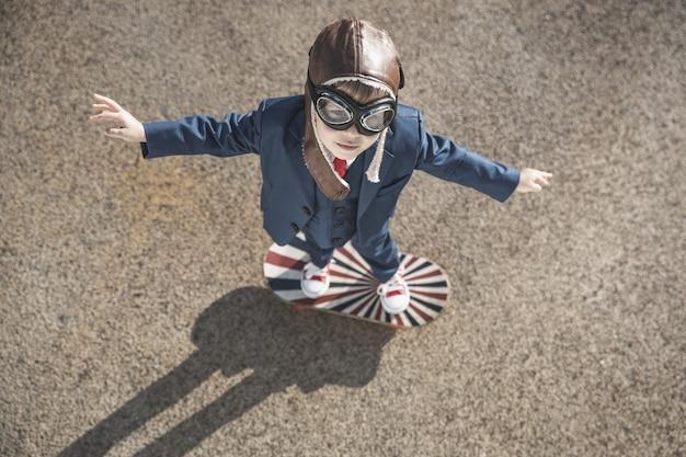屋外でおもちゃの羽で遊ぶ面白い子。