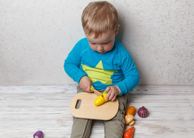 Funny child plays in the chef. smiling baby boy cuts wooden vegetables. interesting safe developing children's game close up. little boy play with plastic toy kitchen.