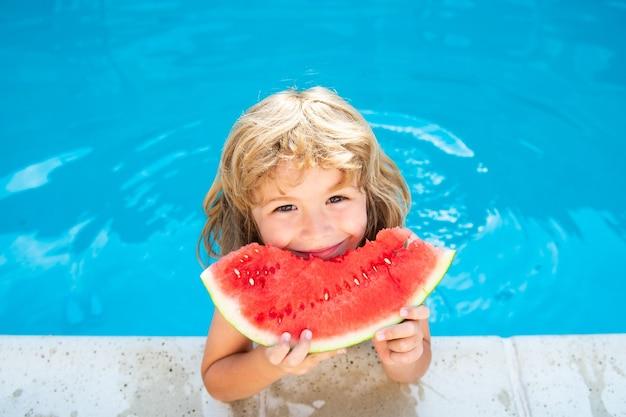 재미있는 아이가 수영장에서 놀고 있습니다. 아이는 달콤한 수박을 먹고 여름을 즐기십시오. 평온한 어린 시절.