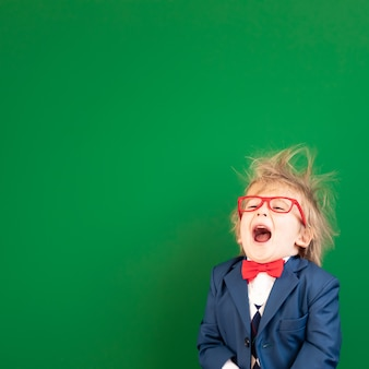 Funny child student in class against green chalkboard.