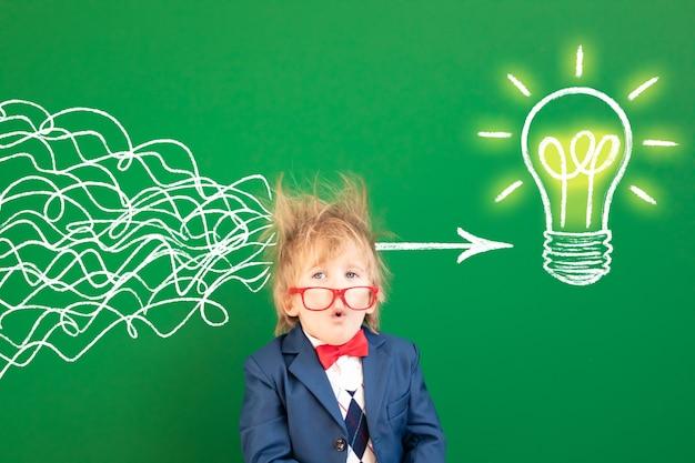 Забавный ребенок-студент в классе. удивленный ребенок против зеленой доски.