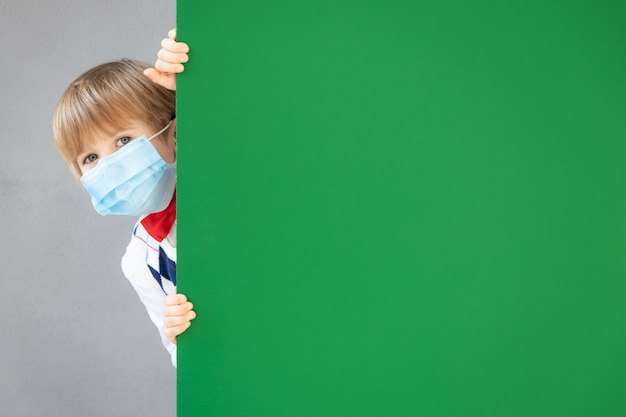 Забавный ребенок-студент в защитной маске в классе. счастливый ребенок прячется за зеленой классной доской.