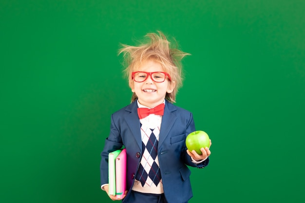 Funny child student with apple and textbook in class against green chalkboard.