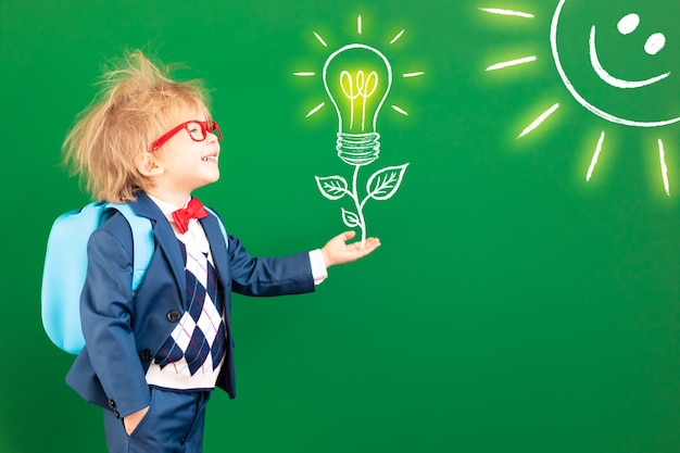 Funny child student with backpack in class against green chalkboard.