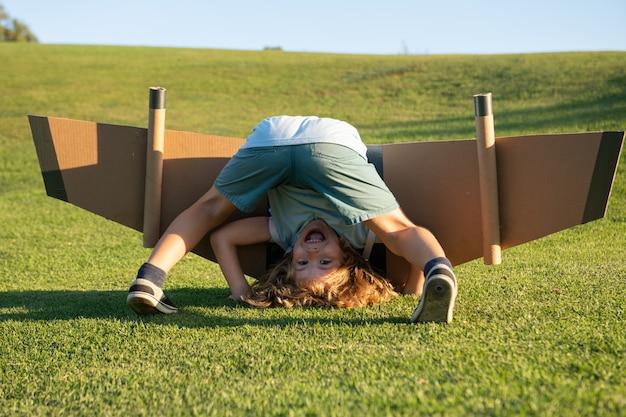 草の上に逆さまに面白い子。子供の頃の想像力、冒険旅行への子供の夢。子供との旅行や休暇。子供の自由とのんきなコンセプト