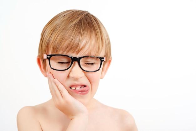 白い背景の上の眼鏡をかけている面白い子。幸せな子供時代。舌を見せているオタク少年。表情と感情。
